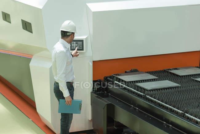 Coordenador que trabalha na fábrica, prendendo a verificação-lista e a supervisão. — Fotografia de Stock