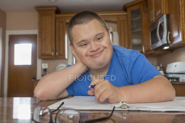 Adolescent avec trisomie 21 étudiant à la maison . — Photo de stock