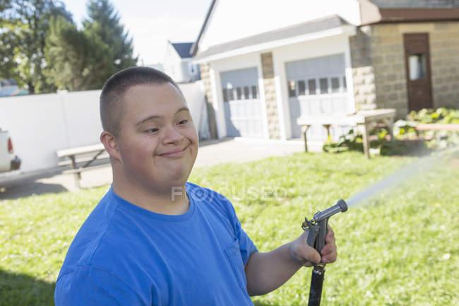 Подросток с синдромом Дауна проведения садовый шланг. — стоковое фото