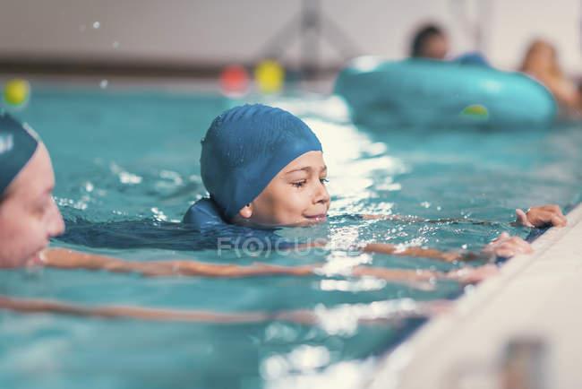 Ragazzo in classe di nuoto con istruttore in piscina pubblica. — Foto stock