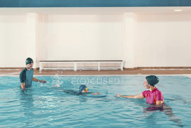 Ragazzo in classe di nuoto con istruttori in piscina. — Foto stock