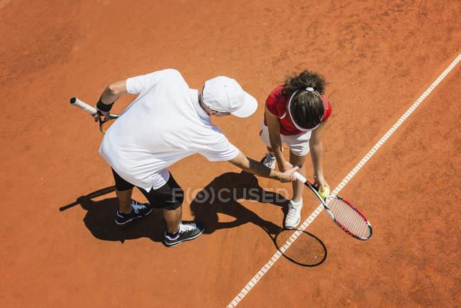 Тренер по теннису, работающий с ученицей-подростком . — стоковое фото