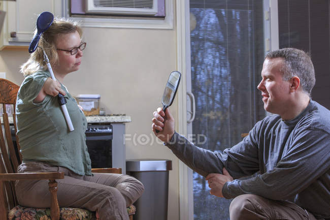 Woman with TAR syndrome brushing hair while husband holding mirror. — Stock Photo