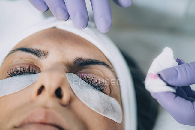Cosmetologist performing lash lift on female patient in salon. — стоковое фото