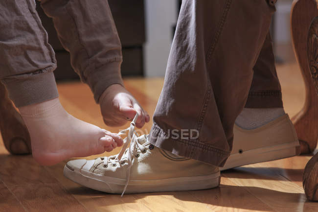 Primo piano della donna con sindrome di TAR che lega le scarpe maschili con i piedi . — Foto stock