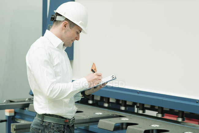 Engineer working in factory, holding check-list and supervising. — Stock Photo