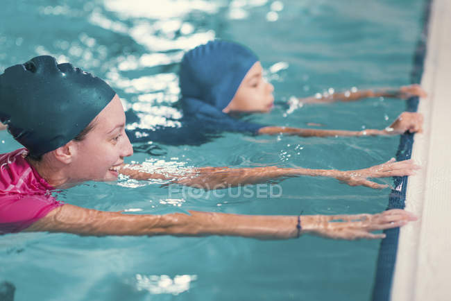 Boy in swimming class with instructor in swimming pool. — Stock Photo