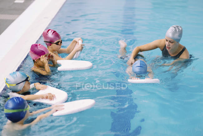 Swimming instructor working with boy while kids watching in swimming pool. — Stock Photo
