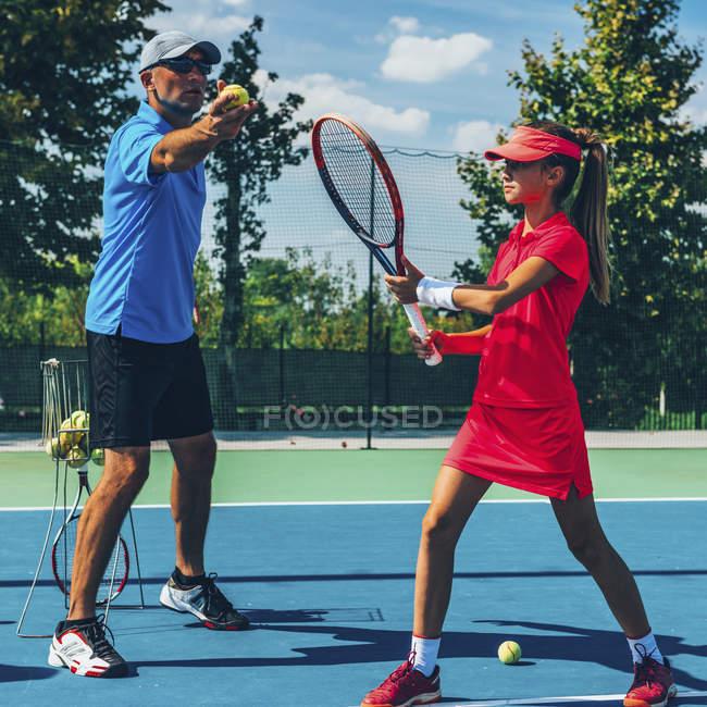Adolescente jogador de tênis praticando com instrutor do sexo masculino em classe de tênis . — Fotografia de Stock