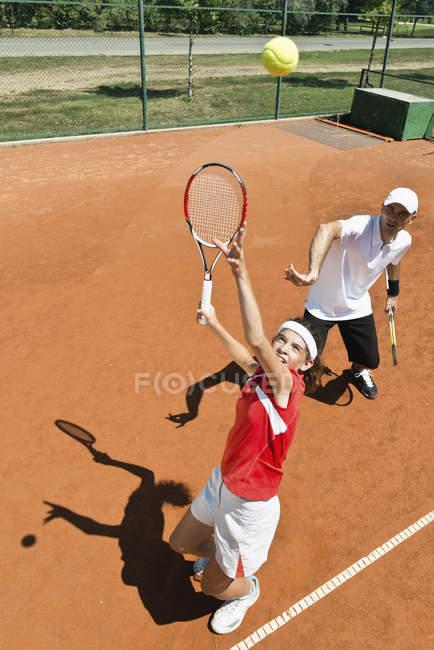 Jogador de tênis adolescente que pratica serviço com instrutor . — Fotografia de Stock