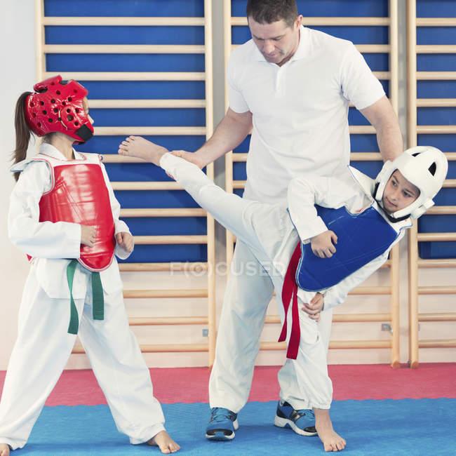 Istruttore che spiega la tecnica dei calci per i bambini in classe. — Foto stock