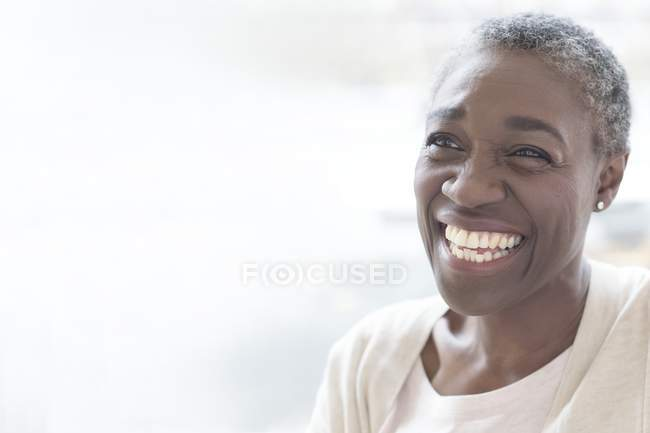 Mature woman smiling and laughing, studio shot. — Stock Photo
