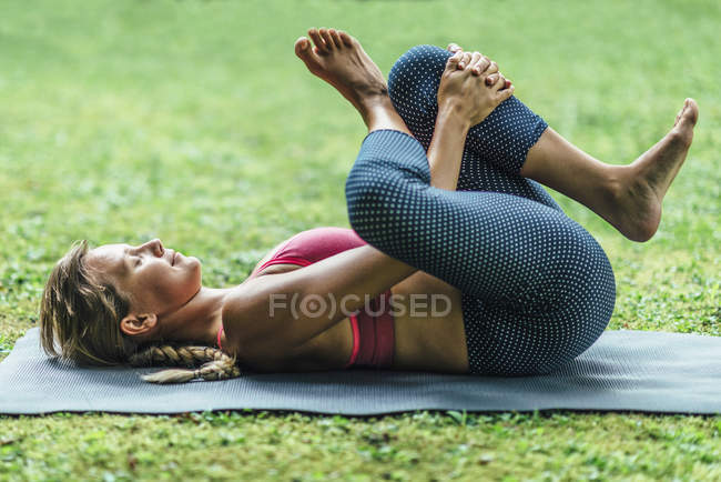 Young woman doing yoga, practicing reclining position on mat in park. — Stock Photo