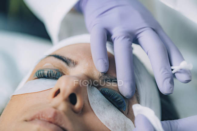Cosmetologist putting black paint on patient eyelashes during lash lifting and laminating procedure. — стоковое фото