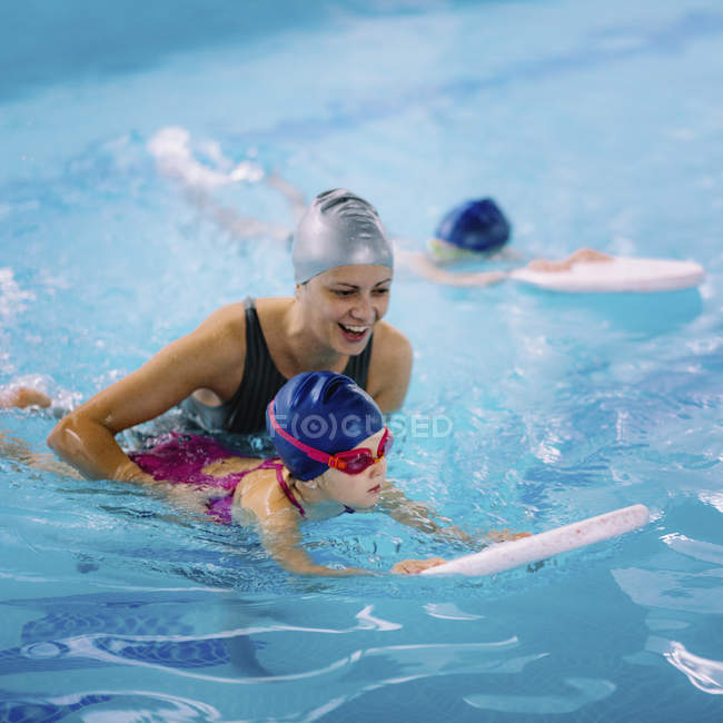 Female instructor working with little girl in swimming pool. — Stock Photo