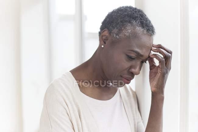 Mujer madura tocando la frente con expresión pensativa . - foto de stock