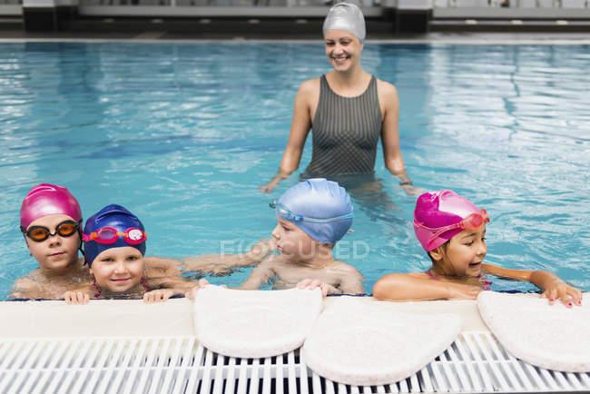 Bambini in classe di nuoto con istruttore femminile in piscina. — Foto stock