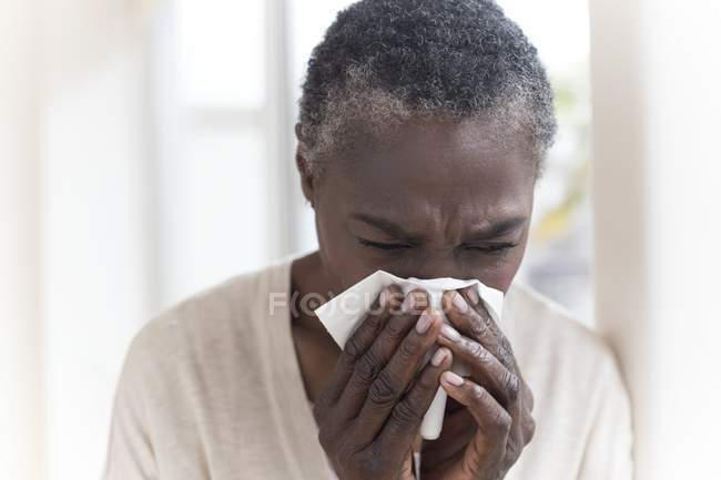 Sick mature woman sneezing into tissue. — Stock Photo