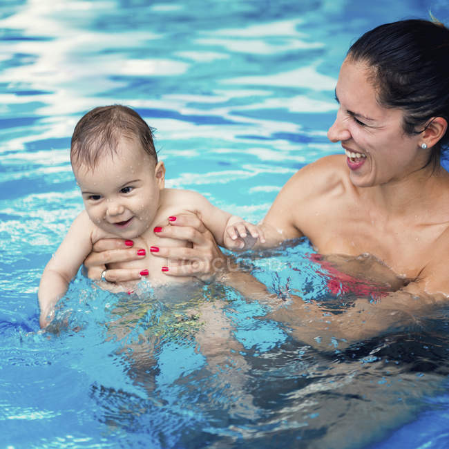 Baby boy and mother in swimming pool water. — Stock Photo
