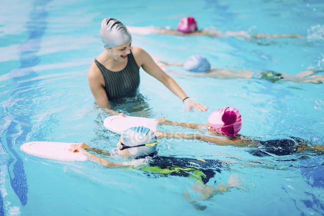 Moniteur de natation avec enfants utilisant des planches à pied dans la piscine . — Photo de stock
