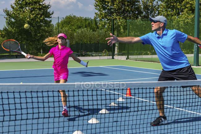 Adolescente em treinamento de tênis na quadra com instrutor masculino . — Fotografia de Stock