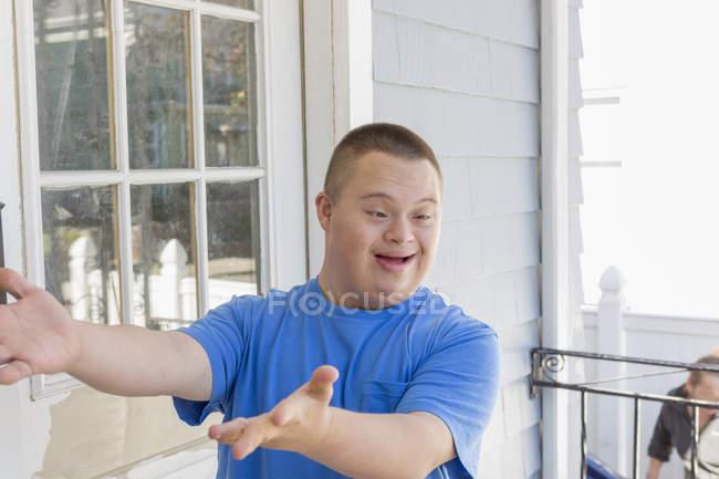 Adolescente con Sindrome di Down gesticolare sul balcone costruzione . — Foto stock