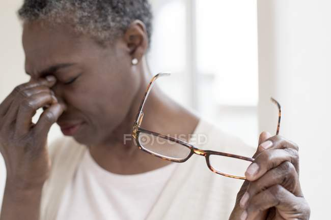 Mature woman with tension headache holding glasses. — Stock Photo
