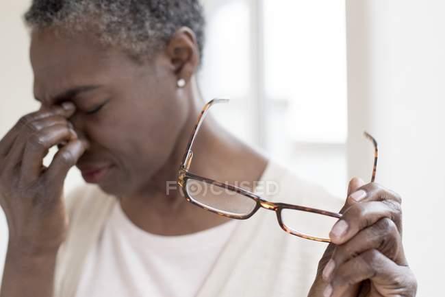 Mujer madura con dolor de cabeza tensión sosteniendo gafas . - foto de stock
