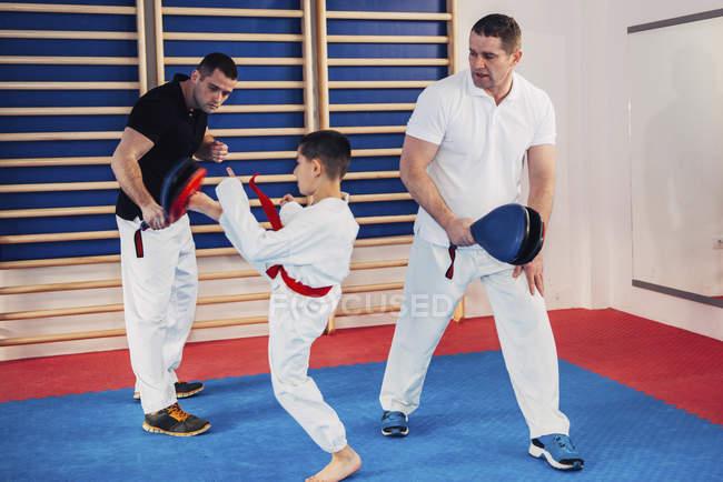 Istruttori di Taekwondo che allenano il bambino in classe. — Foto stock
