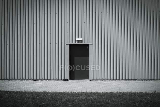 Puerta anónima en el lado del edificio industrial . - foto de stock