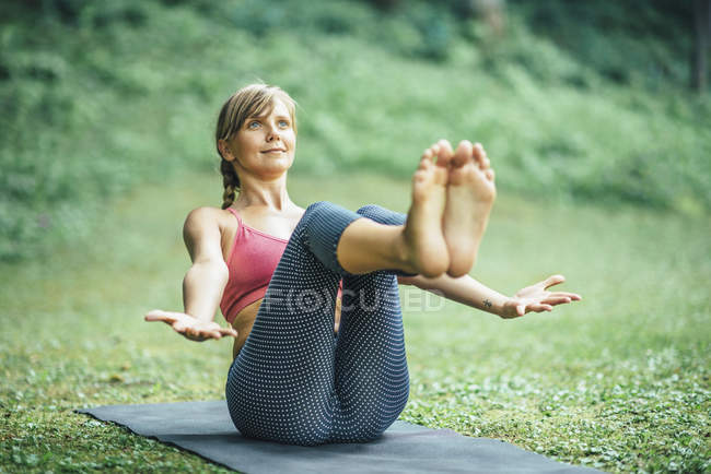 Young woman doing yoga and practicing navasana boat pose on mat in park. — Stock Photo
