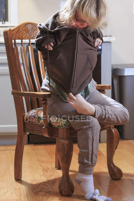 Woman with TAR syndrome putting on jacket and zipping with feet. — Stock Photo