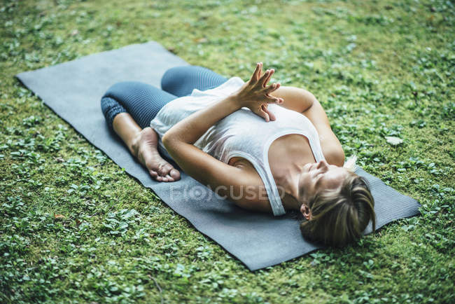 Yoga woman meditating with knees bent and hands in prayer position on mat in park. — Stock Photo