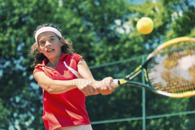 Teenage tennis player hitting ball backhand. — Stock Photo