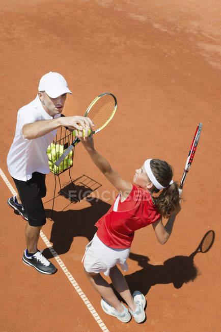 Jogador de tênis adolescente em treinamento com treinador praticando serviço . — Fotografia de Stock