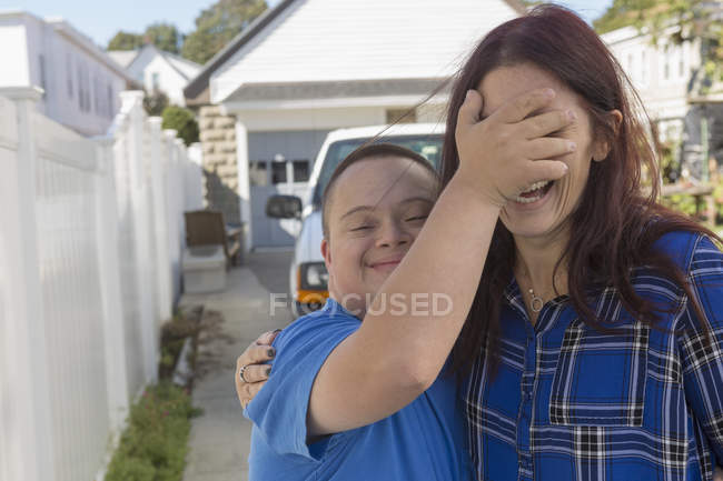 Teenage boy with Down Syndrome playing with female friend. — Stock Photo