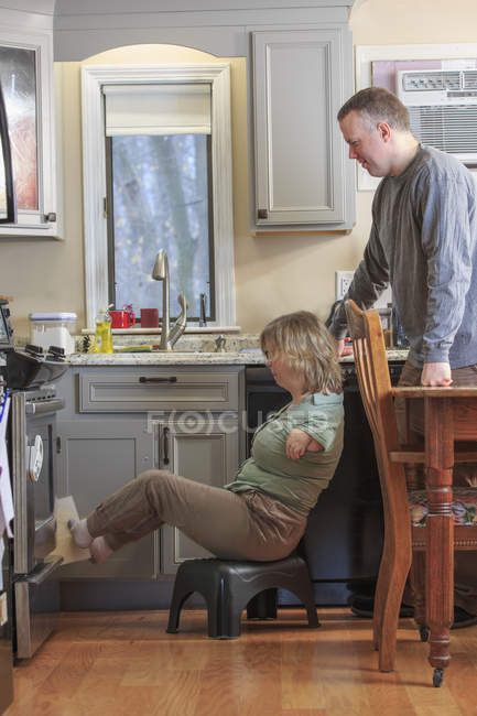 Frau mit Teersyndrom und Mann arbeiten gemeinsam in Küche. — Stockfoto