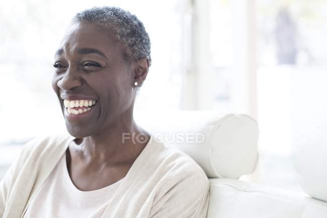 Літня жінка посміхається і сміятися в приміщенні. — стокове фото