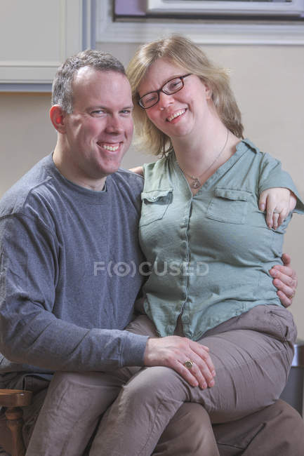 Woman with TAR syndrome sitting on husband lap. — Stock Photo