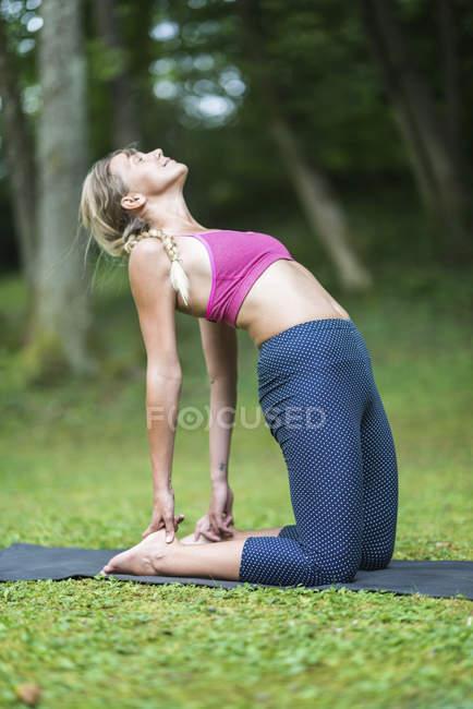 Женщина, практикующая устасанскую верблюжью йогу, позирует на коврике в парке. — стоковое фото