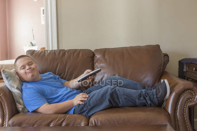 Teenage boy with Down Syndrome lying on couch with TV remote. — Stock Photo