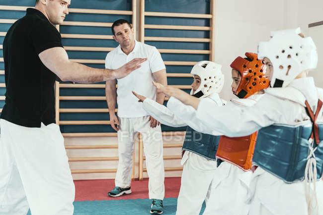 Istruttori di taekwondo che lavorano con i bambini in classe. — Foto stock