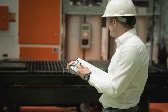 Coordenador que trabalha na fábrica. Segurando a lista de verificação e supervisionando. — Fotografia de Stock