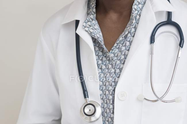 Midsection of mature female doctor wearing stethoscope around neck. — Stock Photo