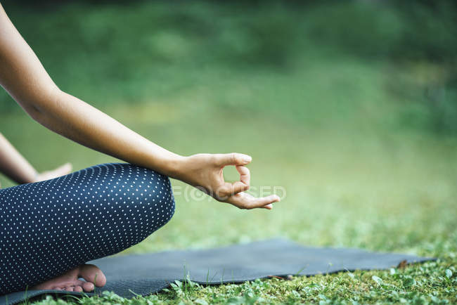 Yoga detail, woman in lotus position with mudra on mat in park. — Stock Photo