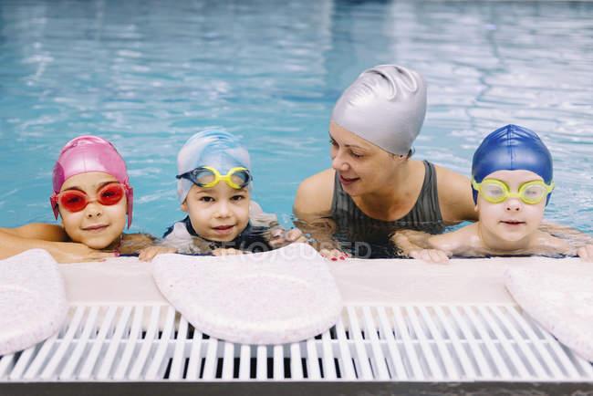 Bambini carini che hanno lezione con istruttore in piscina. — Foto stock