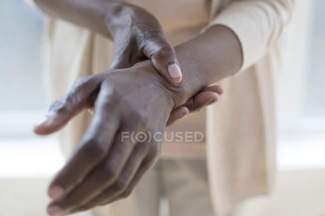 Nahaufnahme der Hände einer reifen Frau mit schmerzhaftem Handgelenk. — Stockfoto