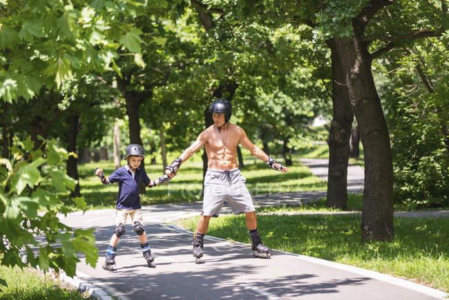 Rapaz patinação no parque com o avô . — Fotografia de Stock
