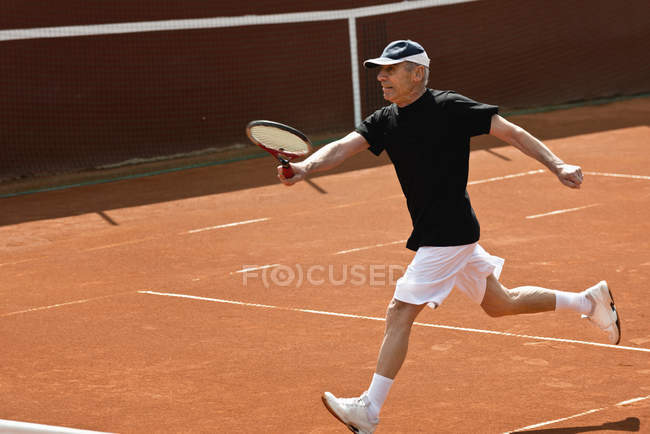 Active senior tennis player running with racket on court. — Stock Photo