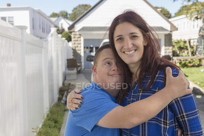 Teenage boy with Down Syndrome hugging female friend. — Stock Photo